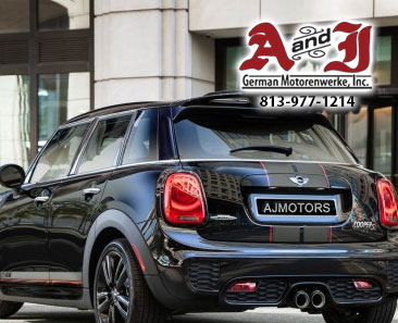 Forest Green 4 door Mini Cooper backside facing grey garage with AJ Motors in License Plate with A&J Logo with Phone 1-813-977-1214