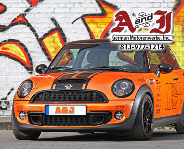 Extremely Orange Mini Cooper with Grafiti Paint Along the Sides Backdrop Grafiti Wall with A&J logo and phone number 1-813-977-1214
